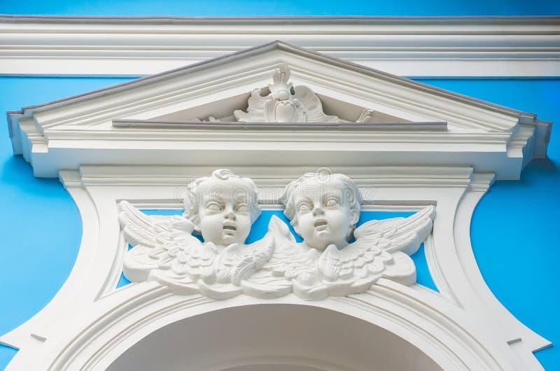 Die Gesichter der Engel über dem Stuckfenster auf der Kirchenwand lizenzfreies stockbild
