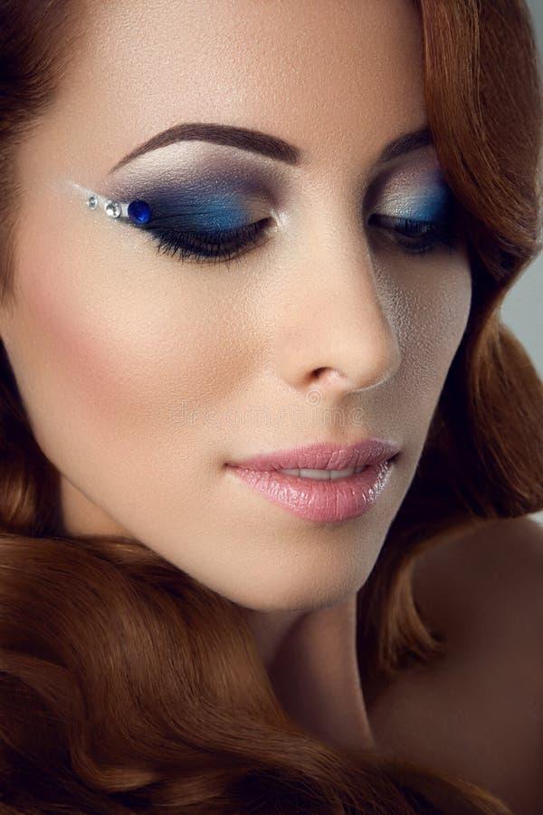 Die Gesichtsnahaufnahme des Mädchens s mit langem Schwarzem peitscht blaues Modemake-up stockfoto