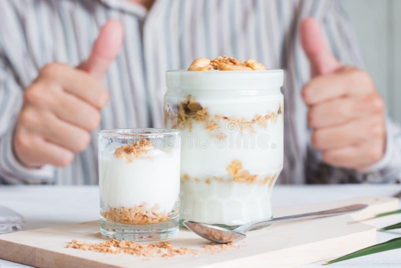 Die gesunde Mahlzeit, die vom Granola im Glas gemacht werden, der Jogurt und die Corn-Flakes verzieren Nahrung mit Acajounuss lizenzfreies stockbild