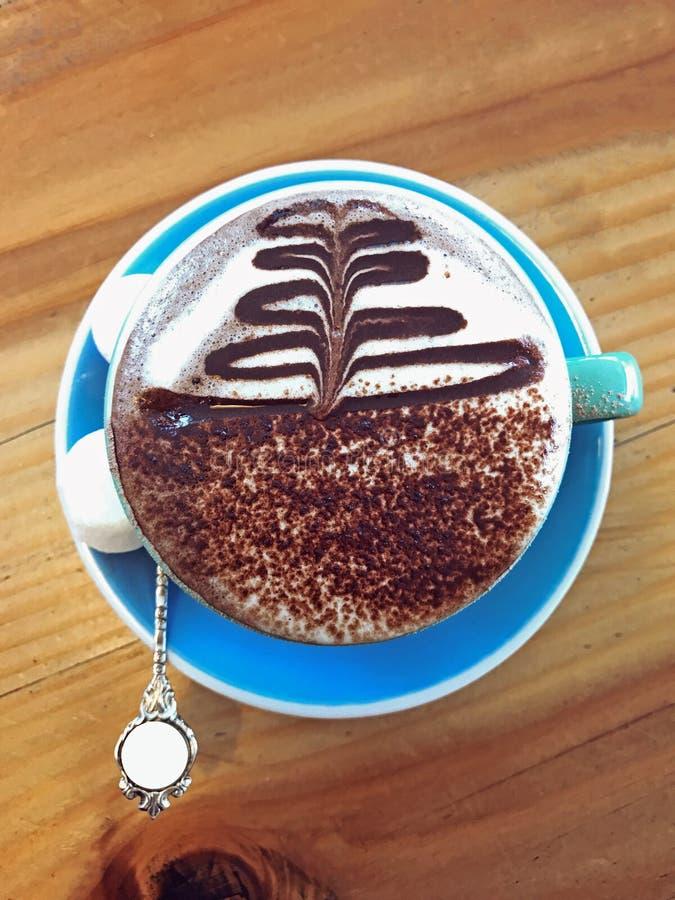 Die Getränk-heiße Schokolade, die mit Sämlingsbild auf Milch Latte verziert wird, schäumen Kunst mit Eibisch in der blauen Becher lizenzfreie stockfotos