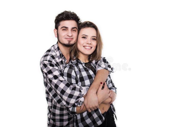 Die glücklichen jungen Paare, die sich umfassen, lokalisierten auf Weiß stockfotos