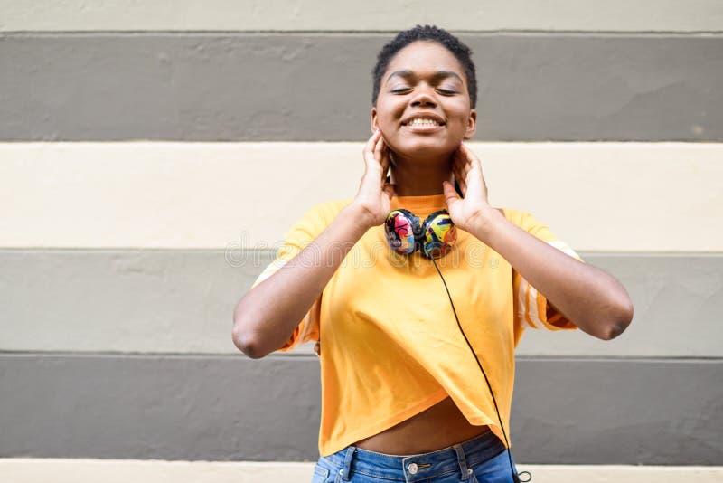 Die glückliche Afrikanerin, die auf städtischer Wand mit Augen lächelt, schloss und trug zufällige Kleidung und Kopfhörer stockbild