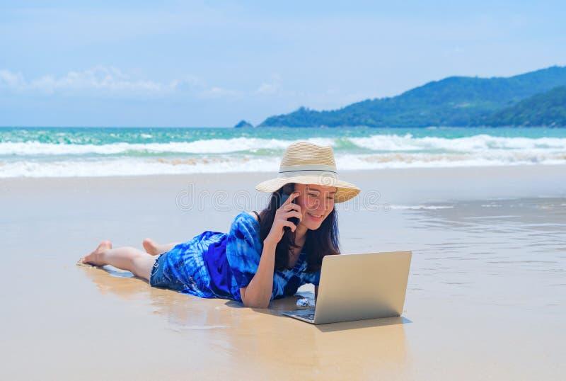 Die glückliche Asiatin, die einen Computerlaptop am Strand während der Reisefeiertage verwendet, machen draußen in Ozean oder Nat stockfoto