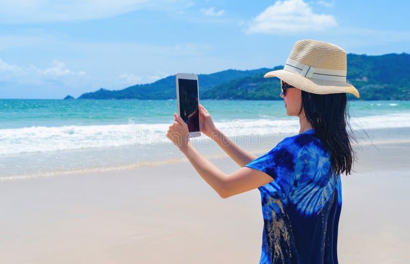 Die glückliche Asiatin, die Handy verwendet, um ein Foto durch Kamera auf Social Media am Strand während der Reisefeiertage zu ma lizenzfreie stockbilder