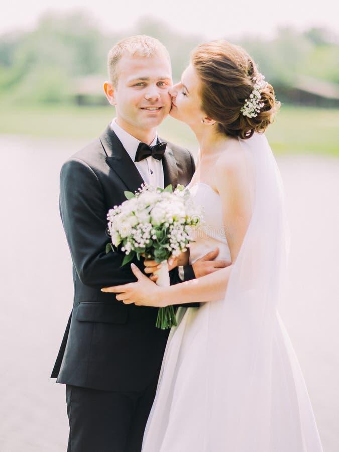 Die glückliche Braut küsst den lächelnden Bräutigam am Hintergrund des Flusses stockfotos