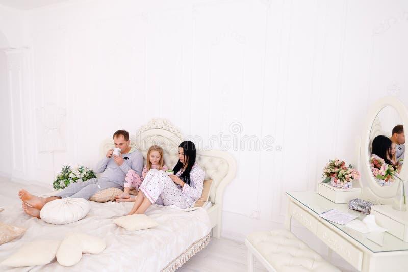 Die glückliche Familie trinkt Tee oder Kaffee in den Pyjamas lächelnd und schauend lizenzfreie stockfotografie