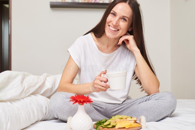 Die glückliche Frau in den Pyjamas gesundes Frühstück genießend lächelt zu seiner lizenzfreies stockbild