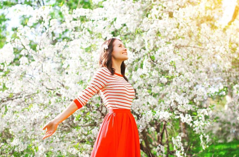Die glückliche Frau, die Geruch genießt, blüht über Frühlingsgarten stockfotografie