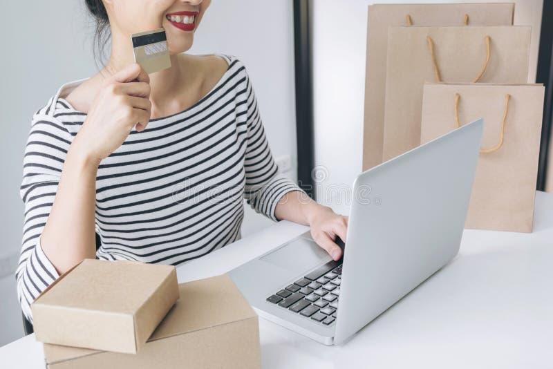 Die glückliche Frau, die intelligentes Telefon verwenden und die Kreditkarte registrieren Zahlungen lizenzfreies stockbild