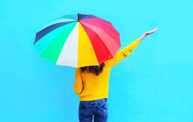 Die glückliche Frau mit buntem Regenschirm hob Hände oben genießend am Herbsttag über buntem blauem Hintergrund an lizenzfreie stockfotos