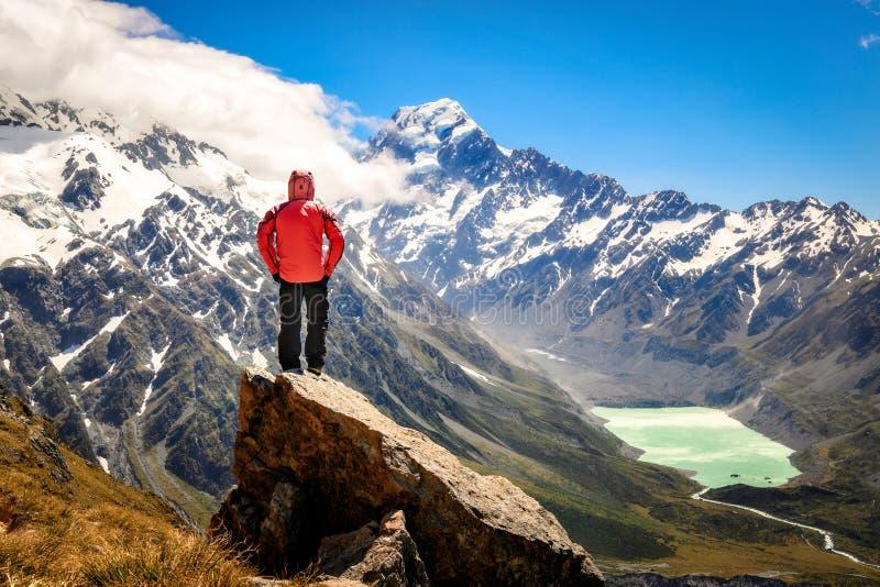 Die glückliche freie touristische Mannstellung, die herauf das Betrachten von Fluss ausgestreckt werden und die Berge gestalten v lizenzfreies stockbild