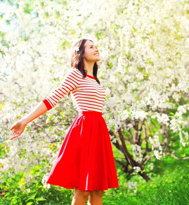 Die glückliche hübsche Frau, die Geruch genießt, blüht über Frühlingsgarten lizenzfreie stockfotos