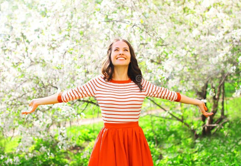 Die glückliche hübsche lächelnde junge Frau, die Geruch genießt, blüht stockbilder