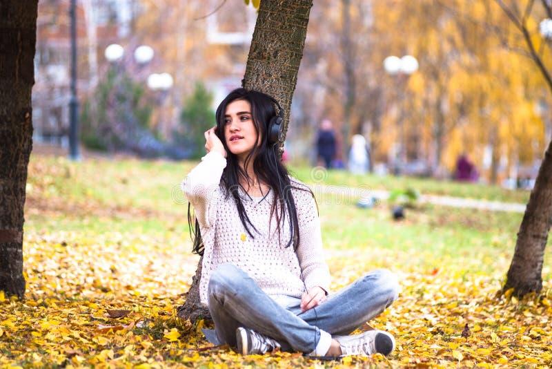 Die glückliche jugendlich Frau, die Musik hört und entspannen sich im Herbstpark Gelbe Bäume, schöne Abfallzeit lizenzfreie stockfotos
