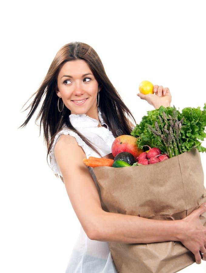 Die glückliche junge Frau, die eine Einkaufstasche voll von den Lebensmittelgeschäften hält, tragen Früchte lizenzfreie stockfotos