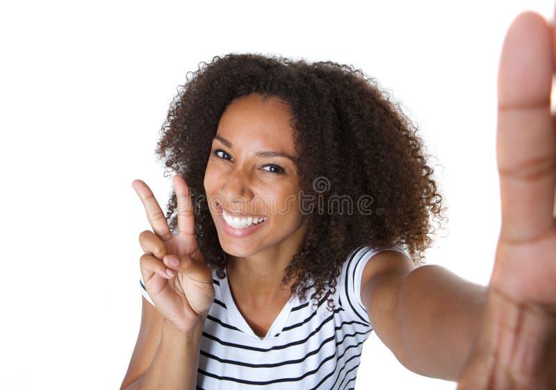 Die glückliche junge Frau, die Frieden zeigt, unterzeichnen herein selfie stockbild