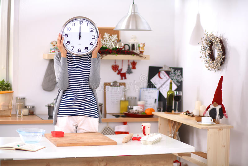 Die glückliche junge Frau, die Uhr im Weihnachten zeigt, verzierte Küche stockfoto