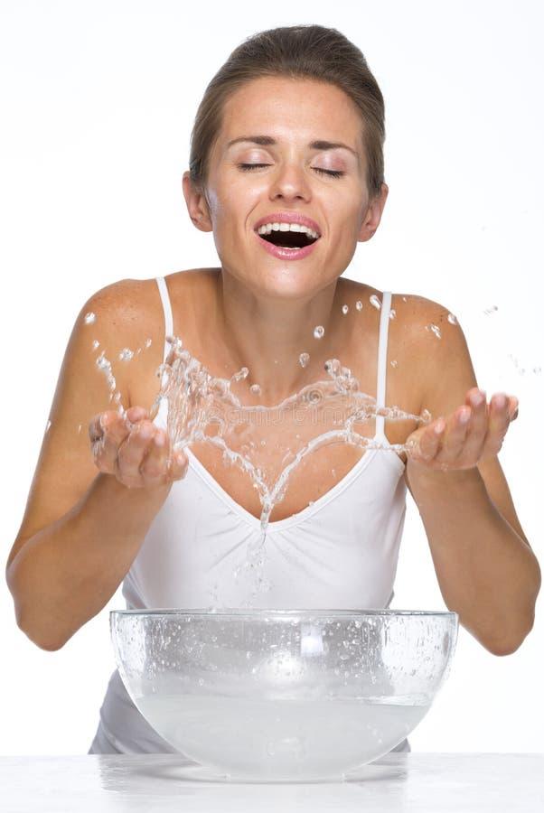 Die glückliche junge Frau, die Wasser macht, spritzt beim Waschen des Gesichtes lizenzfreie stockbilder