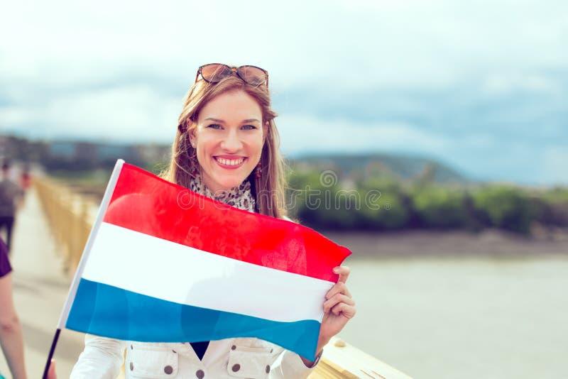 Die glückliche junge Frau, die niederländische Flagge hält, ordnete lizenzfreies stockfoto
