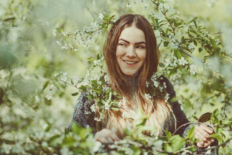 Die glückliche lächelnde junge Frau in einer gestrickten Jacke Frühling genießend blüht im Garten lizenzfreies stockbild