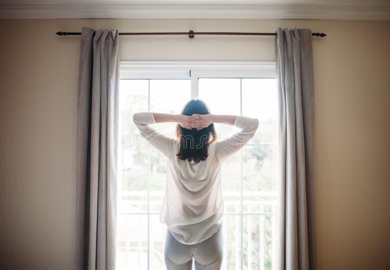 Die glückliche Schönheit, die nahe Fenster nach ausdehnt, wachen auf stockfotos