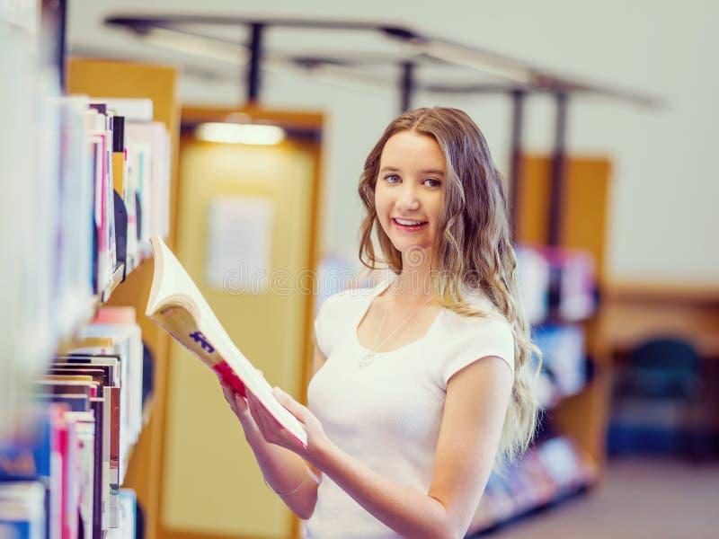 Die glückliche Studentin, die aufhebt, bucht an der Bibliothek stockfotografie