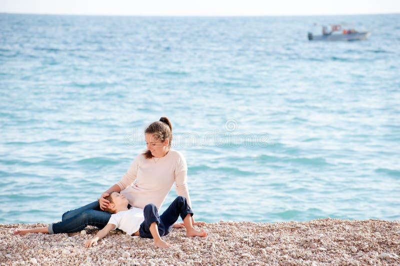 Die glückliche träumende Familie, die aus Mutter bestehen und das kleine Kind, das auf Meer stillsteht, setzen mit Boot auf Horiz lizenzfreies stockfoto