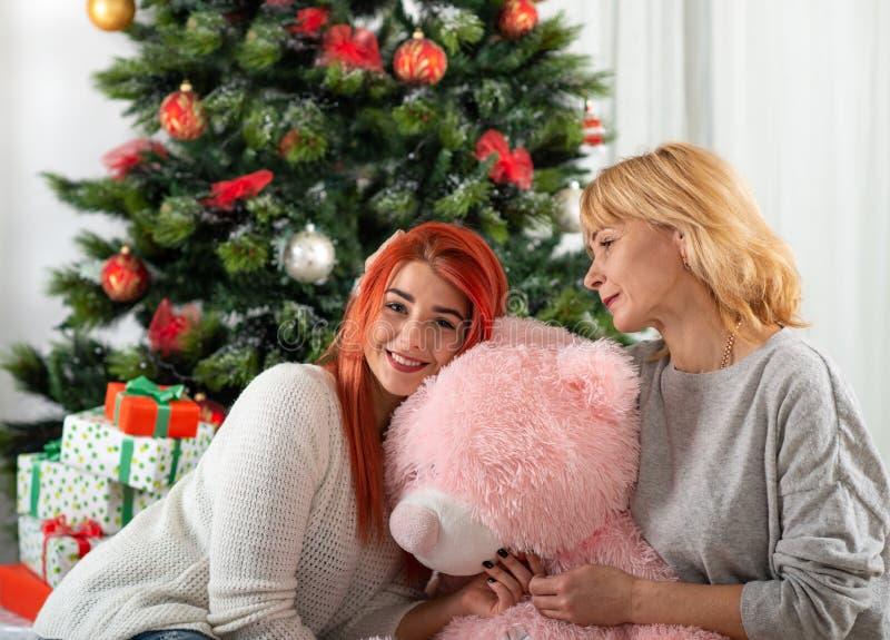 Die glückliche und lächelnde Mutter mit der Tochter sitzen bei einem Christma stockfotos