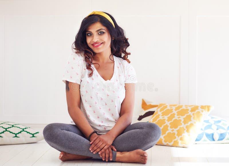 Die gl?ckliche und sch?ne junge Frau, die auf dem Boden sitzt, bereiten f?r Yogaklasse vor stockfotografie