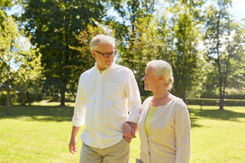 Die glücklichen älteren Paare, die an der Sommerstadt gehen, parken stockfotos