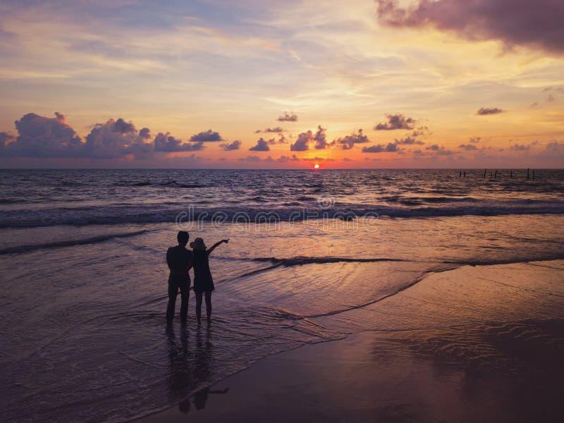 Die glücklichen asiatischen Paare, die am Strand während der Reiseflitterwochenreise an den Feiertagen datieren, machen draußen U lizenzfreie stockbilder