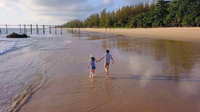 Die glücklichen asiatischen Paare, die am Strand während der Reiseflitterwochenreise an den Feiertagen datieren, machen draußen U stockfotografie