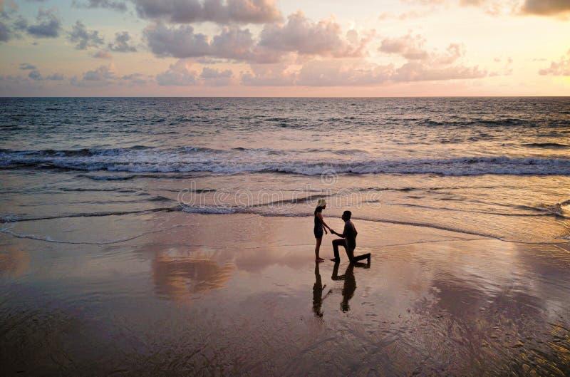 Die glücklichen asiatischen Paare, die am Strand während der Reiseflitterwochenreise an den Feiertagen datieren, machen draußen U lizenzfreie stockfotos