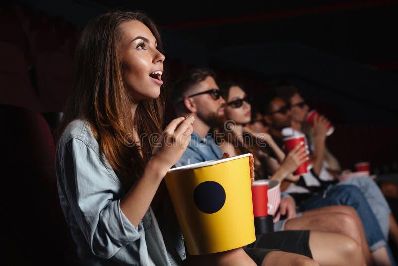 Die glücklichen Freunde, die im Kino sitzen, passen Film auf, Popcorn zu essen stockfotografie