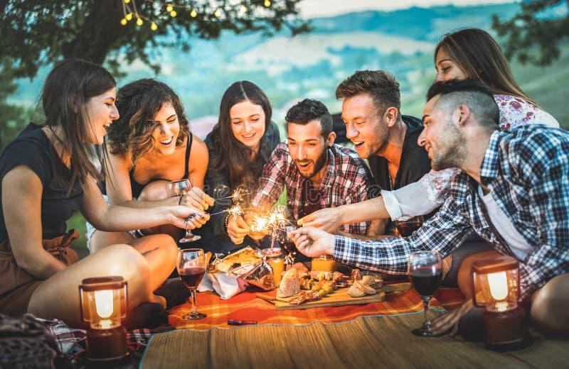 Die glücklichen Freunde, die Spaß mit Feuer haben, funkelt - junge Leute millennials lizenzfreies stockbild