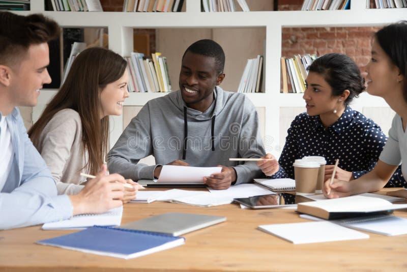 Die glücklichen gemischtrassigen jungen Leute haben Spaß zusammen studierend stockfotos