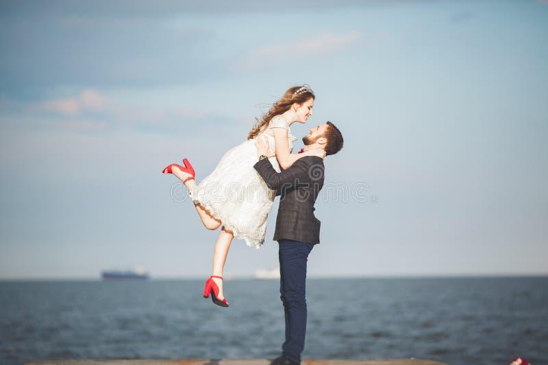 Die glücklichen gerade verheirateten jungen feiernden Hochzeitspaare und haben Spaß bei schönem Strandsonnenuntergang stockbild