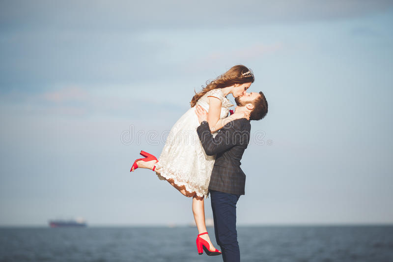 Die glücklichen gerade verheirateten jungen feiernden Hochzeitspaare und haben Spaß bei schönem Strandsonnenuntergang lizenzfreie stockfotografie