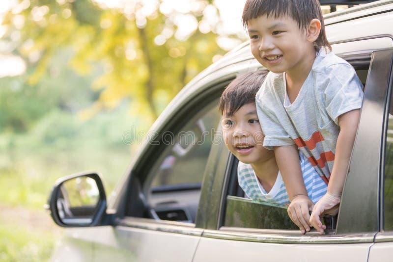 Die glücklichen Geschwister, die Hände wellenartig bewegen, reisen mit dem Auto gegen blauen Himmel Sommerautoreisekonzept stockbild