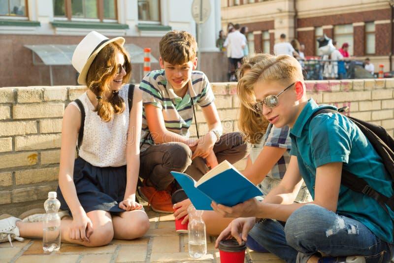 Die glücklichen 4 Jugendfreunde oder hohe Schüler haben Spaß und sprechen und lesen Telefon, Buch stockbild