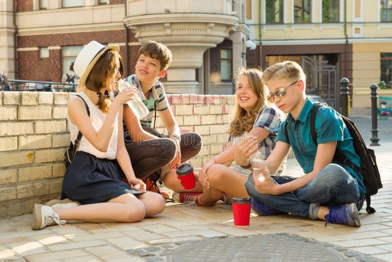 Die glücklichen 4 Jugendfreunde oder hohe Schüler haben Spaß und sprechen und lesen Telefon, Buch Freundschaft und Leutekonzept,  lizenzfreie stockfotos
