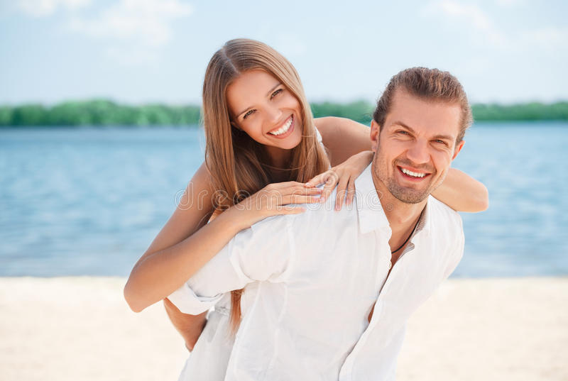 Die glücklichen jungen frohen Paare, die huckepack tragendes zusammen lachen des Strandspaßes während der Sommerferien haben, mac stockbilder