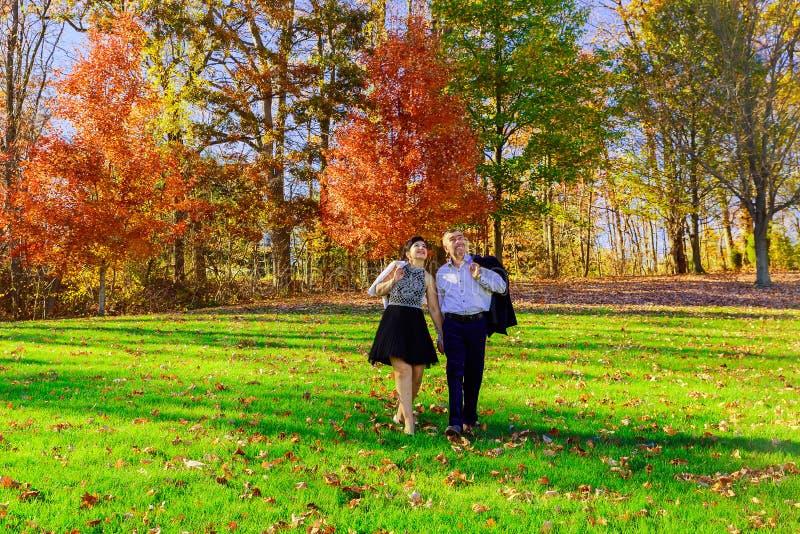 die glücklichen jungen Paare der Liebe, der Verhältnisse, der Jahreszeit und des Leutekonzeptes, die im Herbst umarmen, parken stockbilder