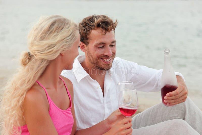 Die glücklichen jungen Paare, die Rotwein draußen trinken, setzen auf den Strand lizenzfreie stockbilder