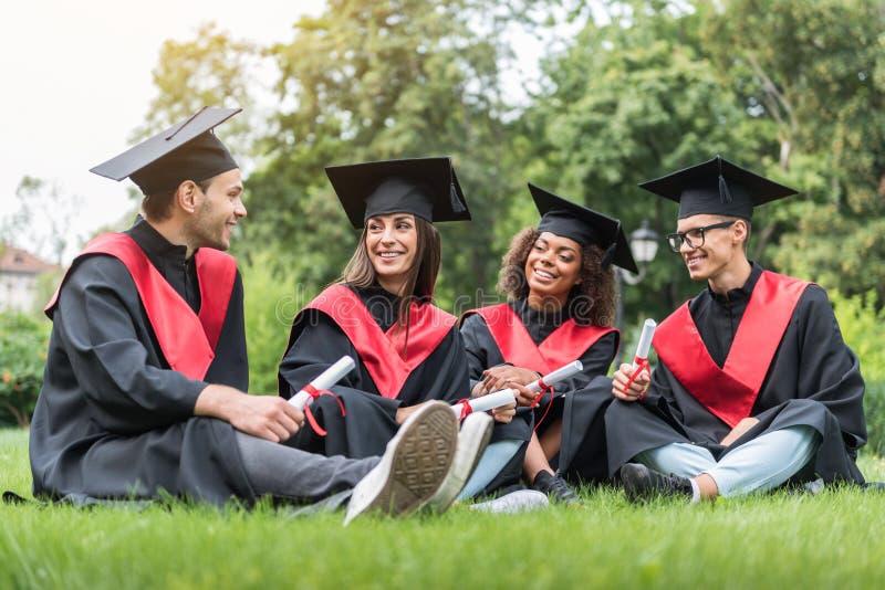 Die glücklichen jungen Studenten, die auf Rasen in der Staffelung sich entspannen, kleidet lizenzfreies stockfoto