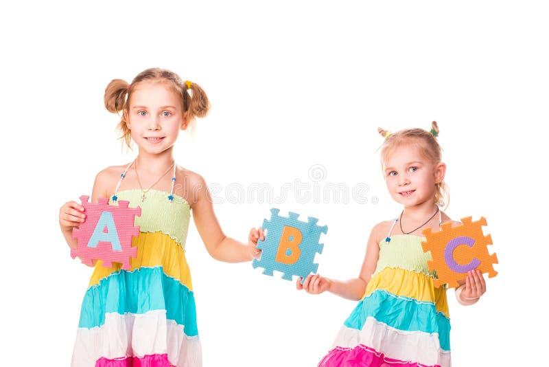 Die glücklichen Kinder, die Alphabet anhalten, bezeichnet ABC mit Buchstaben lizenzfreies stockfoto