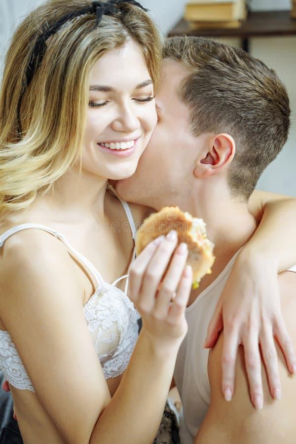 Die glücklichen liebevollen Paare, die Frühstück sind sie genießen, lachend und essend Sandwich und habend die schöne Zeit stockfoto