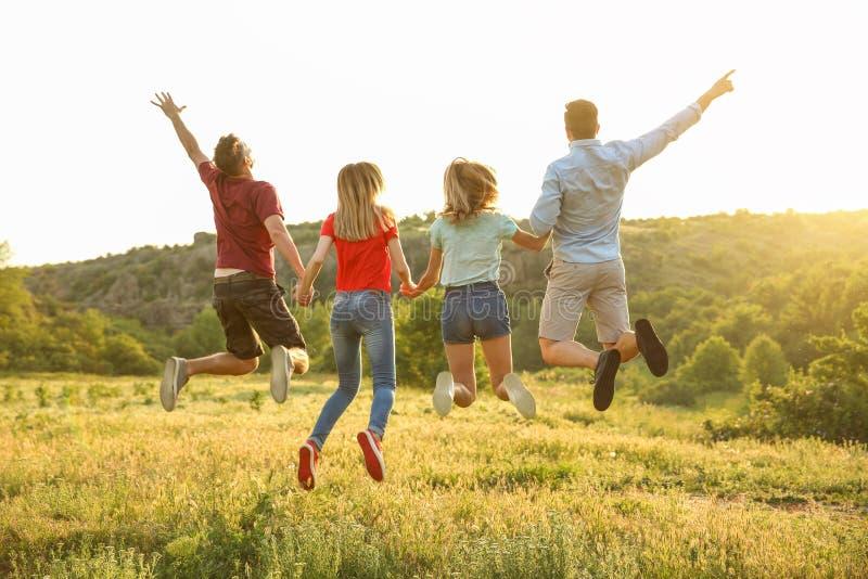 Die glücklichen Menschen springend in Wildnis Kampierende Jahreszeit lizenzfreie stockbilder