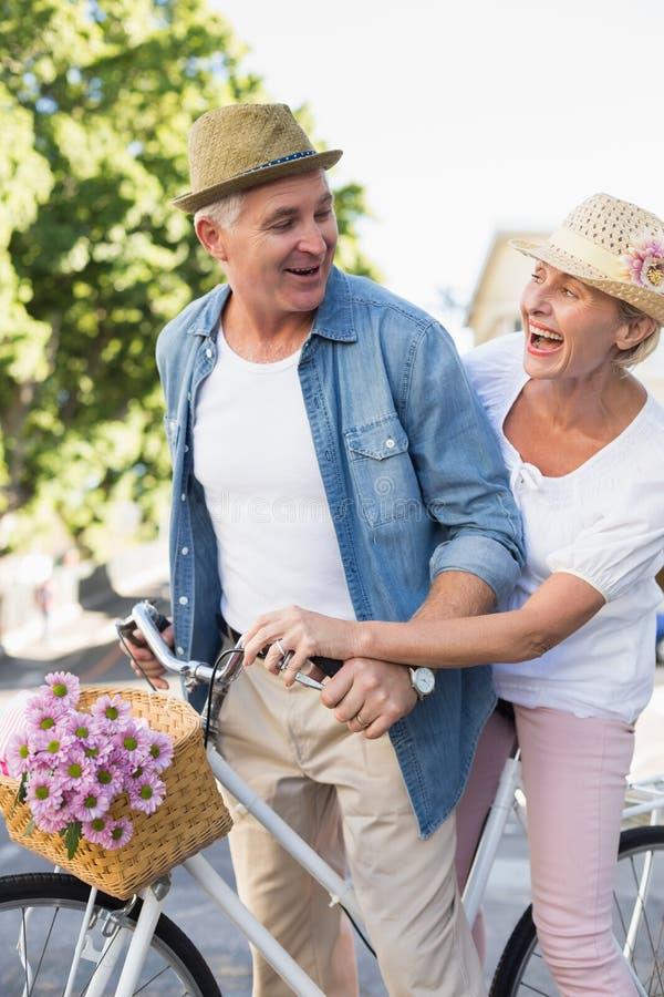 Die glücklichen reifen Paare, die für ein Fahrrad gehen, reiten in die Stadt lizenzfreie stockfotos