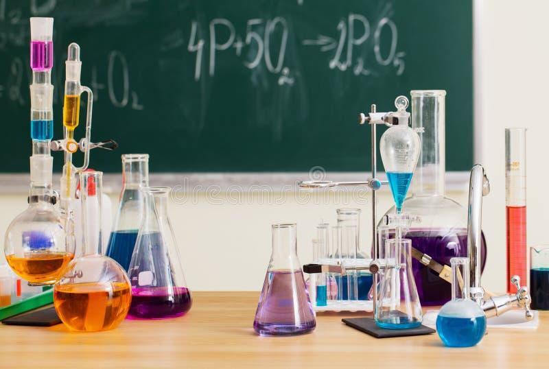 Die Glasflaschen mit mehrfarbigen Flüssigkeiten an der Chemielektion stockfotos